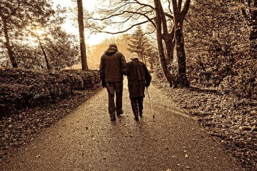 une personne avec sa canne et une seconde personne qui la guide
