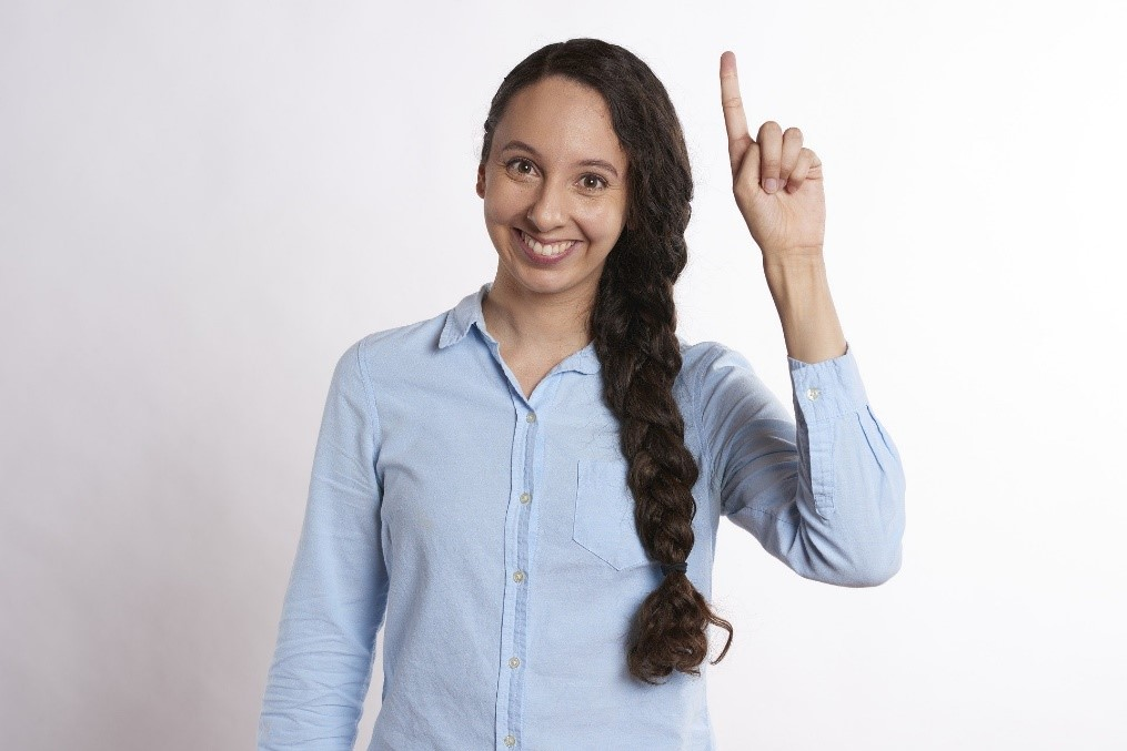 Femme qui sourie et lève le doigt